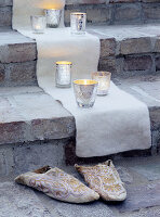Cloth, silver tealight holders and slippers on steps