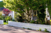 View of front garden of house with low picket fence
