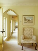 Baroque-style armchair next to open door with arched frame and view into corridor beyond