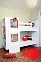 White bunk bed with windows and integrated book shelves in a children's bedroom
