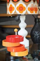 Cake stand with colourful plastic dishes in front of 70s lamp