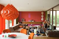 Red, retro pendant lamp above dining area and children on sofa in open-plan living space