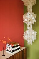 Pendant lamp with mother-of-pearl discs in corner of living room with two different coloured walls