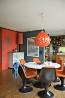 Brown plastic shell chairs with orange cushions and dining table below orange pendant lamp in open-plan room