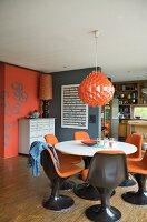 kuhfell neben schalenstuhl vor arbeitsplatz und dunkelbraune wand im 70er jahre stil bild. Black Bedroom Furniture Sets. Home Design Ideas