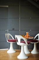 Dining area with white shell chairs and red cushions in front of wall clad in slate slabs