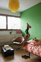 Corner of teenager's room with green-painted wall and swivel chair with brown leather cover next to bed and vintage trunk