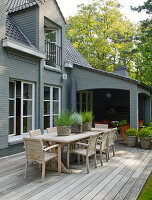 Long wooden table and chairs on terrace of house with grey brick walls