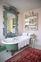 Old-fashioned bathroom in the 'Shabby' look with free standing bathtub, antique mirror and colorful carpet on plank flooring