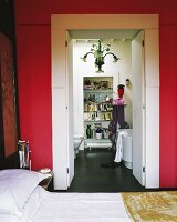 View from red-painted bedroom through open double doors into modern, white bathroom