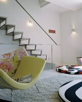 Armchair with green cover in front of modern metal staircase on wall and colourful floor cushions in designer interior