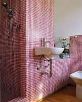 White sink on wall with claret mosaic tiles and open shower area in designer bathroom