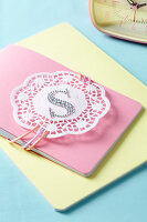 A notebook decorated with a symbol and a doily