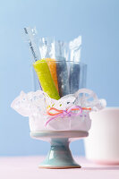 Sticks of coloured sugar in a glass wrapped in a doily on a cake stand