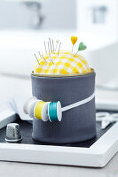 A tin can wrapped in fabric being used as a pin cushion