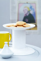 A homemade cake stand made from two plates and a white-painted tin can