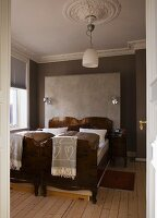 Antique twin beds standing next to one another against grey-painted walls with stucco frieze