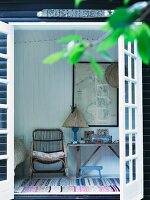View through terrace door of wicker armchair and rustic table