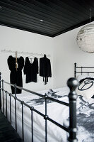 Antique-style metal bed below black-painted wooden ceiling and Japanese paper lampshade; black clothing on hangers in background