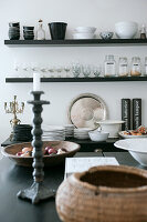 View across kitchen counter to wall-mounted shelf holding antique flea-market finds and black and white crockery