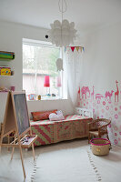 White child's bedroom with animal motifs painted on wall; easel set up in front of bed with patterned bedspread below window
