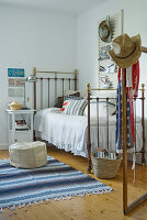 Vintage-style metal bed and striped rug on wooden floor in simple bedroom with American ambiance