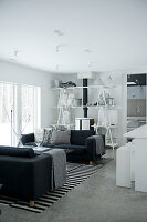 Open-plan, black and white interior with comfortable sofas and original DIY shelving around wood-burning stove