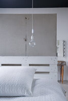 Prefab concrete slabs forming back wall of rustic bed structure made from white-painted pallets and hanging light bulb as bedside lamp