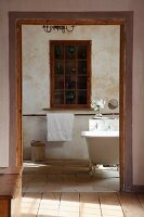 View from anteroom of cabinet with glass and lattice door built into niche in rustic bathroom