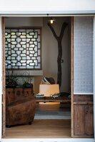View of leather armchair and wooden window lattice in living room through open terrace door