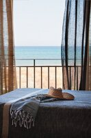 Straw hat on day-bed in front of open balcony door with fluttering curtains and sea view