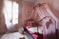 Romantic pink bedroom with wrought iron bed