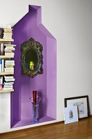 Mirror with ornate frame on wall and glass floor vase in purple-painted niche