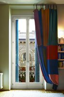 Floor-length curtain in colourful checks at balcony door with view of historic architecture