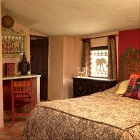 Oriental style bedroom with a low ceiling with a paisley pattern bedspread and decorative wooden elephants