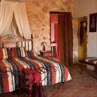 Double bed with a canopy in front of a natural stone wall in a Mediterranean bedroom