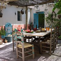 A set table with simple wooden chairs on a covered terrace in Spanish Mediterranean style