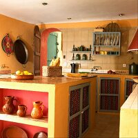 A Mediterranean country house kitchen with built-in, yellow-painted cupboards and clay pots on shelves