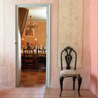 An antique chair in a pink-painted anteroom with a view into a dining room with a festively decorated table