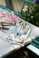 Ladies' gardening gloves with classic French patterns in pink and light blue on old garden table