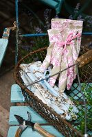 Pristine gardening gloves with feminine French patterns in old wire basket on garden chair