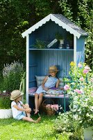 Girl in straw heat sitting in blue, open-fronted garden arbour with bench and shelf in summer garden