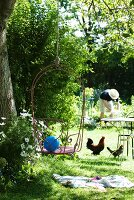 Idyllic garden - wire chair hanging from tree on rope, hens beneath bistro table and person gardening in background