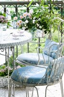 White metal chairs with seat cushions and bistro table in front of flowering plants in wire basket hanging on wrought iron balustrade