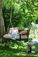 Wooden garden swing with cushions hanging from tree on ropes