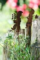Patinated sheet metal garden gnomes on rods next to garden fence