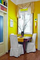 Bold yellow in corner of living room - tiny seating area with white covered chairs at wooden table below window