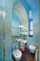 Modern bathroom with Oriental ambiance - mosaic tiles in rounded arch surrounding mirror and bathroom fittings