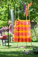 Changing tent in pink and orange 70s fabric next to running garden shower; woman cutting flowers in background