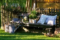 Fresh herbs and pillows on a garden bench, watering cans